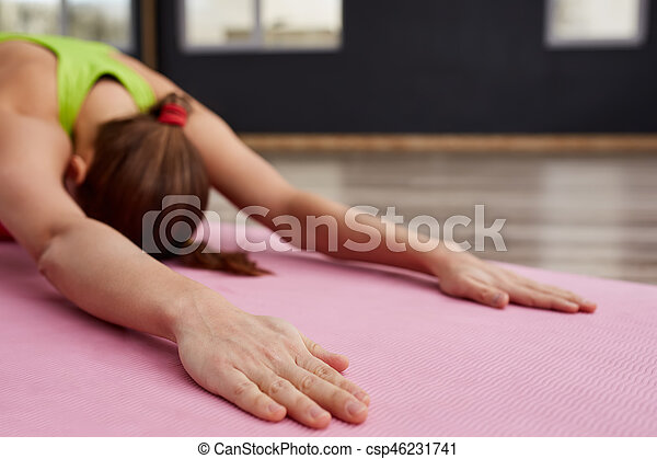 woman on yoga class indoor closeup of hands in relaxing pose. Sporty woman with long hear in sporty clothes. On the pink yoga mat. Closeup of the hands. Blurred background. Healthy lifestyle.