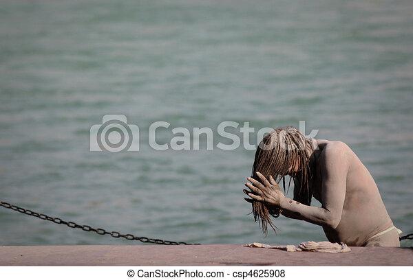 Sadhu rubs his hair with ashes - csp4625908