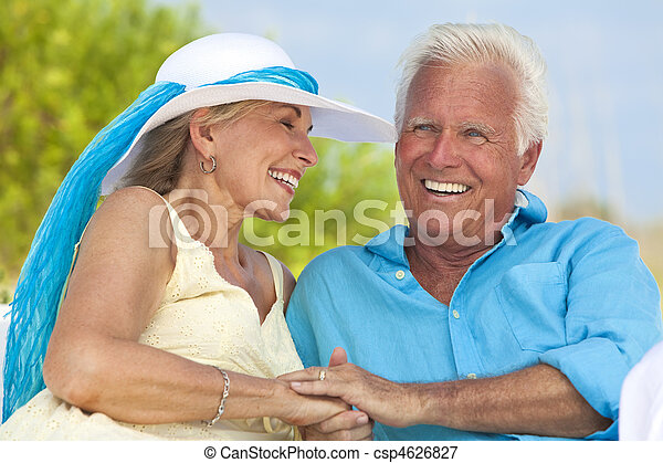 Happy Senior Couple Holding Hands & Laughing at the Beach - csp4626827