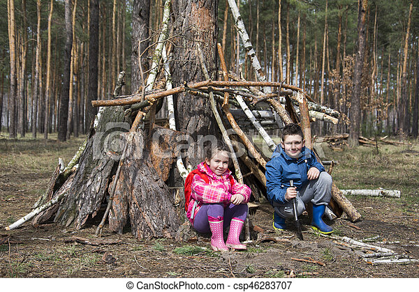 In the spring in the pine forest brother with a little sister they play they built a hut out of sticks.