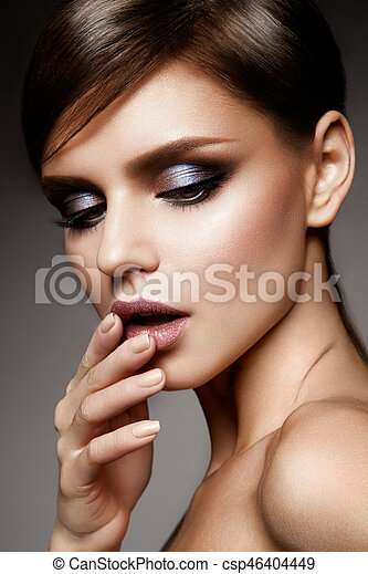 Beautiful young model with bright make-up and hairstyle