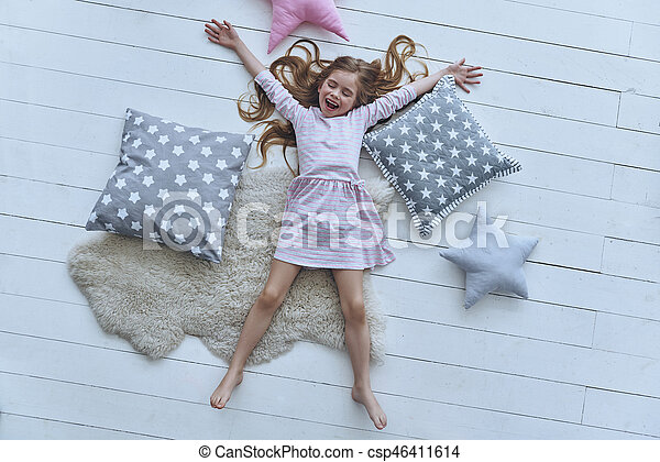 Like a star. Top view of cute little girl keeping eyes closed and smiling while lying on the floor amongst pillows