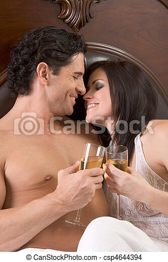 Loving young sensual couple with Champagne in bed - csp4644394