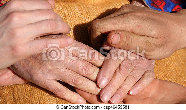 A young man\'s and woman\'s hands comforting a old pair of hands of grandmother outdoor