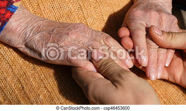 A young male hands comforting an elderly pair of hands of grandma outdoor close up