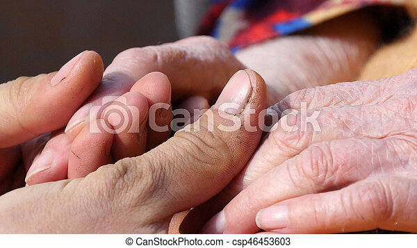 A young man\'s hands comforting an elderly pair of hands of grandmother outdoor close-up.Sun comes out from behind the clouds and highlights their.