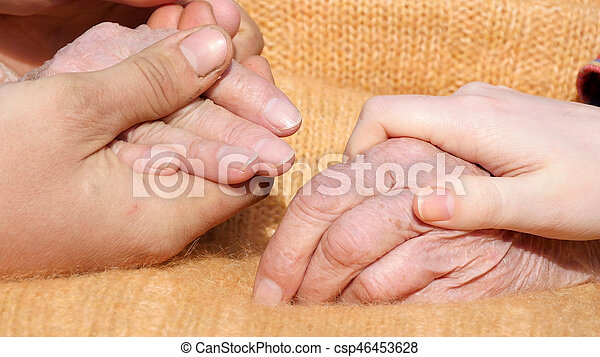 A young male and female hands comforting a old pair of hands outdoor