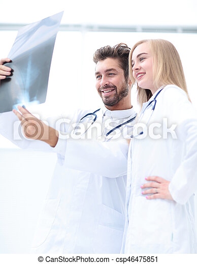 Closeup portrait of intellectual healthcare professionals with white labcoat, looking at full body x-ray radiographic image