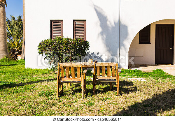 White outdoor furniture. Lounge chairs in hotel garden invite you to relax.