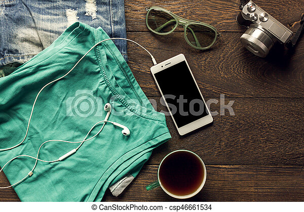 Top view accessories travel with mobile phone,camera,earphones,sunglasses,cloth woman,coffee on table wooden with copy space.Travel concept.