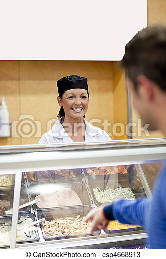 Handsome student showing his choise to the cook in the cafeteria of his campus - csp4668913