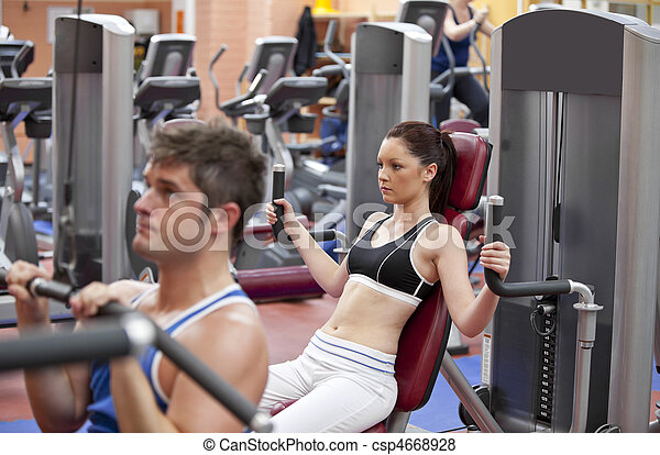 Concentrated couple using shoulder press in a fitness centre - csp4668928