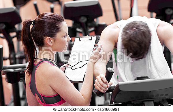 Female coach using a chronometer while man is pedaling on a bicycle in a fitness centre - csp4668991