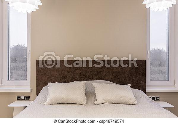 Simple beige bedroom with big bed with brown headboard