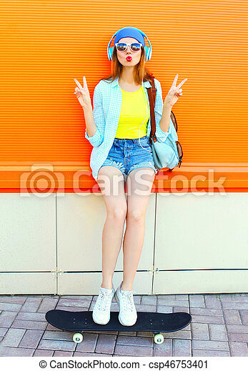 Fashion pretty cool girl is listens to music with a skateboard over colorful orange background
