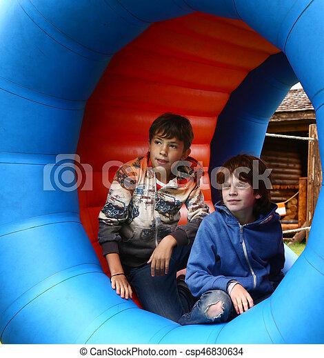 preteen boys in amusement park in rolling rubber barrel close up photo