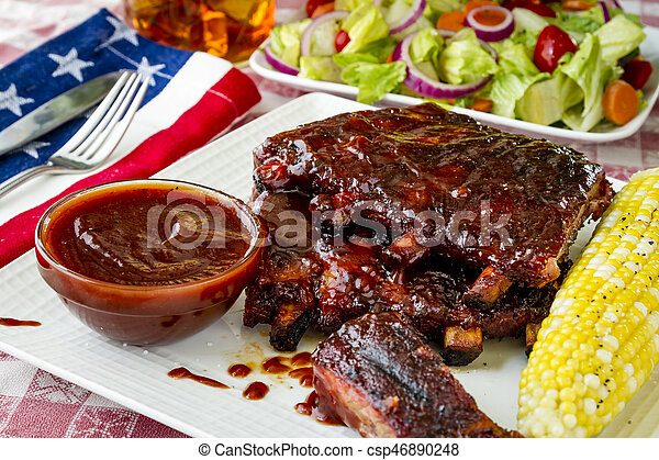 All American picnic with bbq ribs and whiskey bourbon bbq sauce with ear of corn and fresh salad side dish