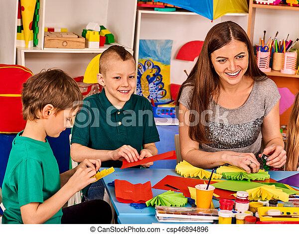 Preschool scissors in kids hands cutting paper with teacher in class room. Development and social lerning happy children in school. Children\'s project in kindergarten. Small group girls together.