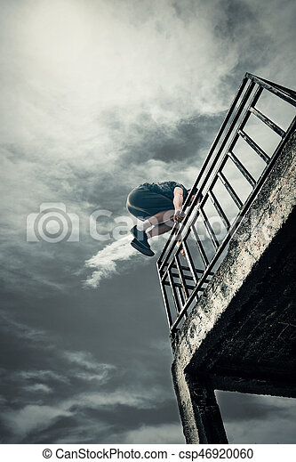 young man doing parkour jump in urban space in the city day time