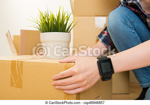 beautiful woman wearing smart watch on hand moving to new house. holding carton boxes. mixed race asian chinese model.