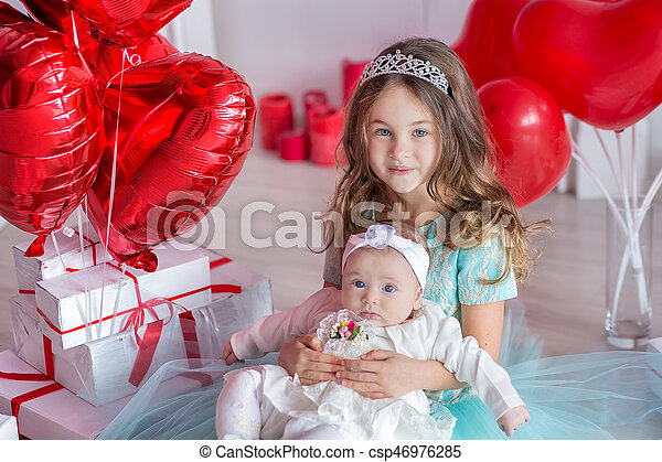 Cute baby girl celebrating birth day together close to red balloons.Lovely scene of baby on sofa divan with presents and red baloons