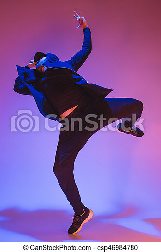 The silhouette of one young hip hop male break dancer dancing on colorful background