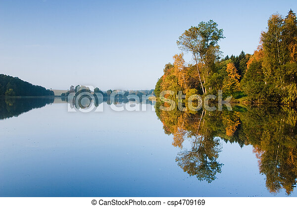 Autumn landscape of pond and bright trees