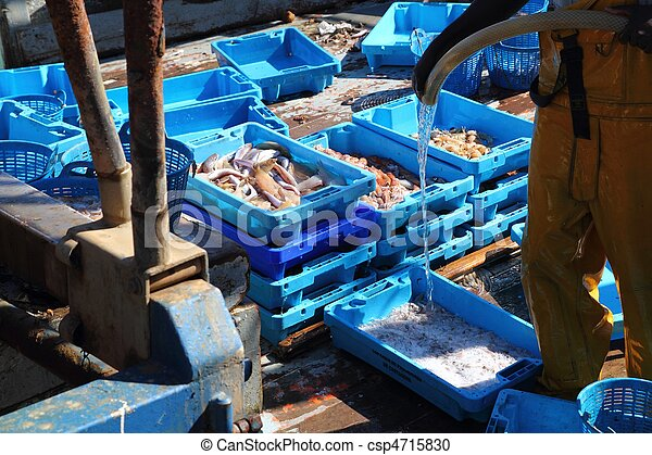fisherman on fisher boat deck cleaning fish boxes - csp4715830