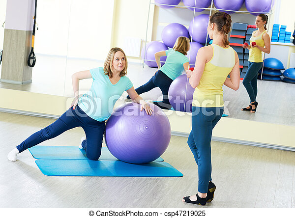 young pregnant woman doing fitness ball exercise with female instructor coach in sport club