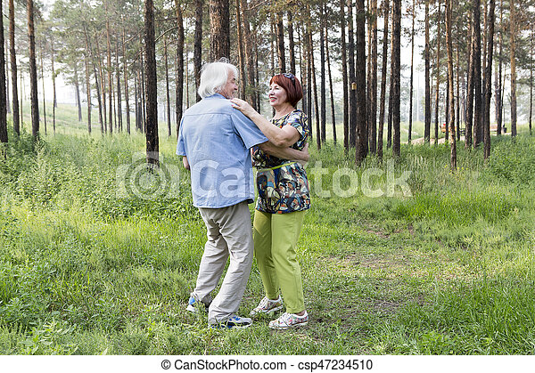 Senior couple, old man and woman in a park on the weekend activities. Senior couple dancing in a summer forest. Grandparents make in the woods. The concept of retirement age and love.