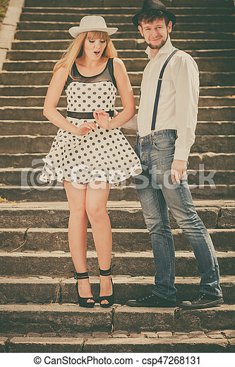 Summer holidays love relationship and dating concept - romantic playful couple retro style flirting on city stairs