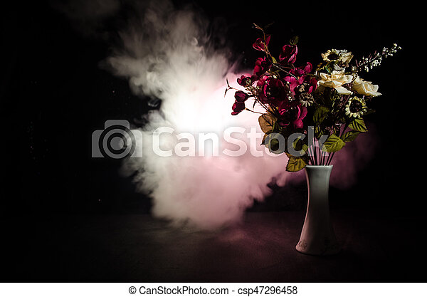 Picturesque purple spring flowers in glass vase standing in a row on a dark background with stars with light and fog. Flower concept with balloon