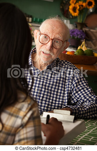 Elderly man in home with care provider or survey taker - csp4732481