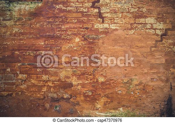 Grunge brick wall with peeling orange paint - csp47370976