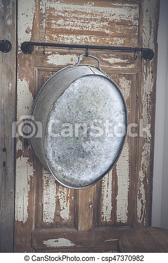 Old stylish iron tub hanging on a wooden wall - csp47370982