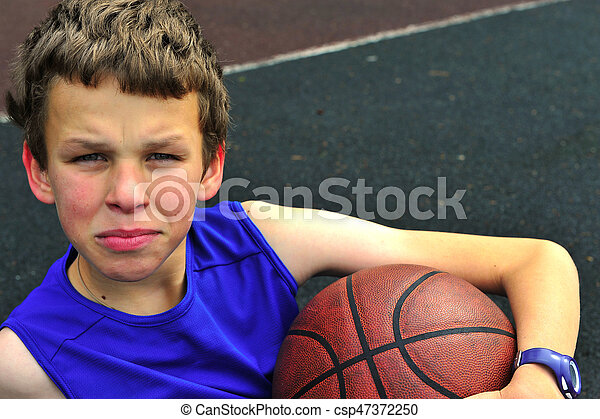 Teenager in blue shirt sitting on the basketball court