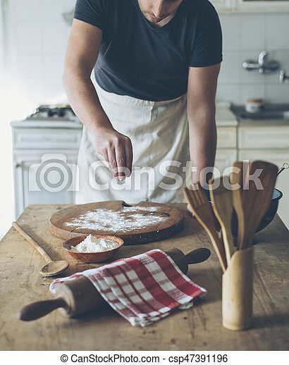 Chef making food on kitchen table. Baker man baking homemade bread dough on vintage wooden board. Retro style image. People cooking in home concept.