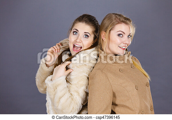 Two women, wearing light brown coat and furry jacket. Winter fashion concept.