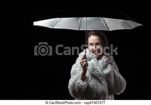 Beautiful woman with fur coat standing in rain under an umbrella at night - csp47407477