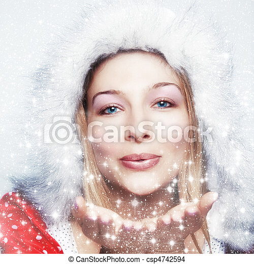 Happy winter woman blowing snowflakes - csp4742594