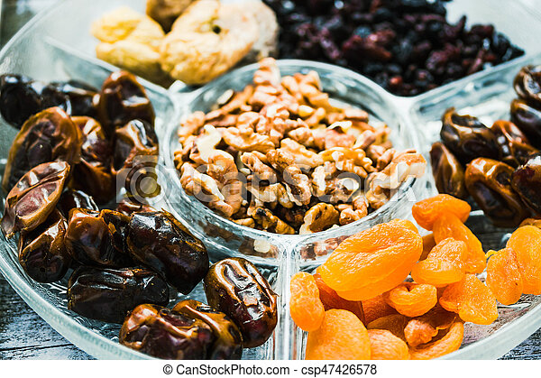 Assorted dried fruits and nuts on a glass plate. Close up. - csp47426578