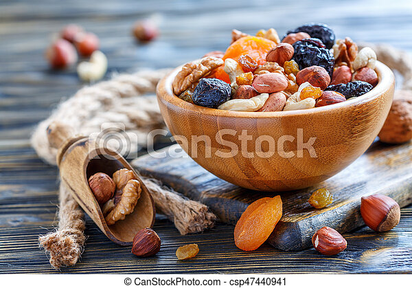 Mixture of nuts and dried fruits in a bowl and scoop on the old wooden table, selective focus.