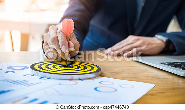 Business Man hand holding a target with darts hitting the center. Concept of personal coaching success. Concept of objective attainment.