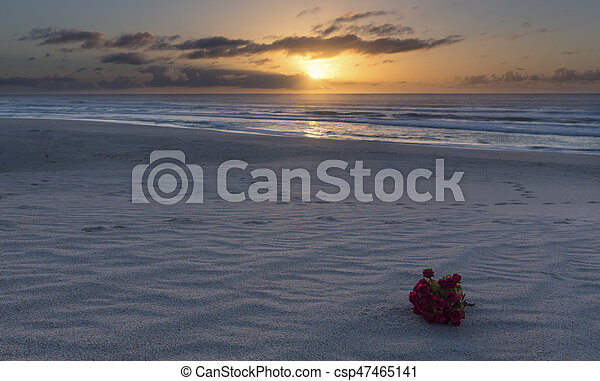 Bouquet of red flowers on beach at sunrise with cloudy sky - csp47465141