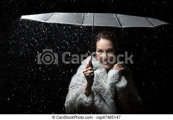 Beautiful woman with fur coat standing in rain under an umbrella at night - csp47465147