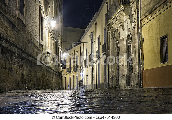Street in Brindisi by night with disappearing couple, Puglia, Italy