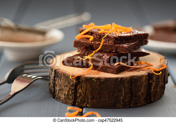 Healthy craft chocolate bars with orange rind on wood slabs - csp47522945