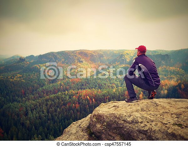 Moment of loneliness. Man in black enjoy marvelous view. Hiker sit on the peak of rock and watching into colorful mist and fog in forest valley.