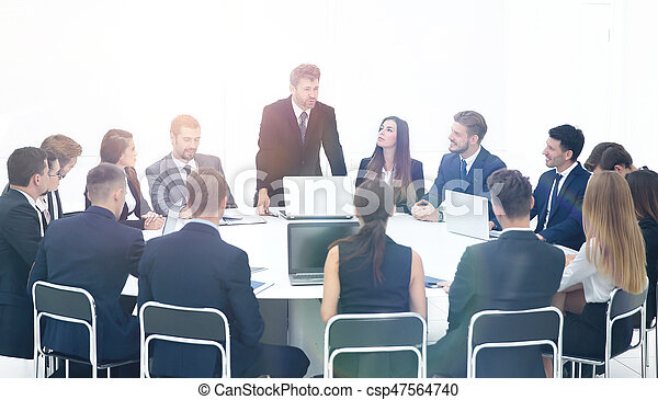 serious leader of a new business project, stands in front of the laptop and holds a meeting with his business team sitting at a large round table
