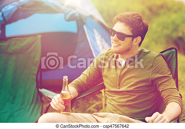 happy young man drinking beer at campsite tent - csp47567642